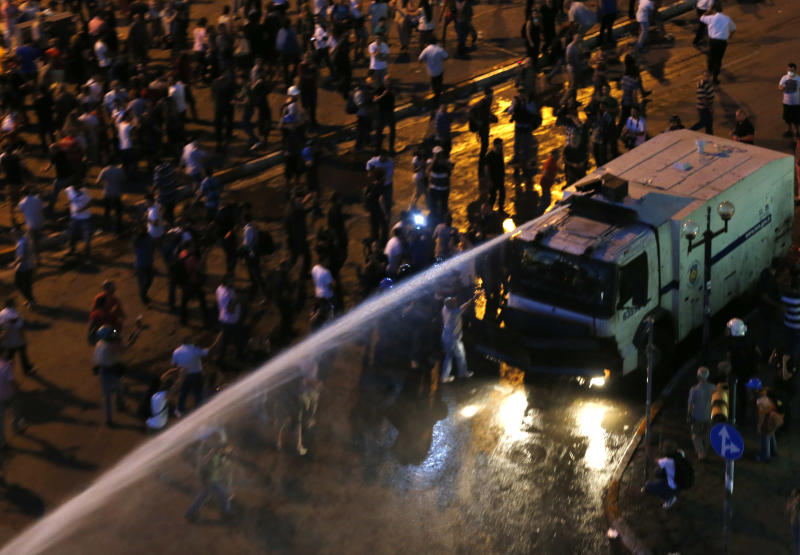 Water canon sprays protesters during clashes at Taksim Square in Istanbul, Turkey, Saturday, June 22, 2013. (AP Photo/Petr David Josek)