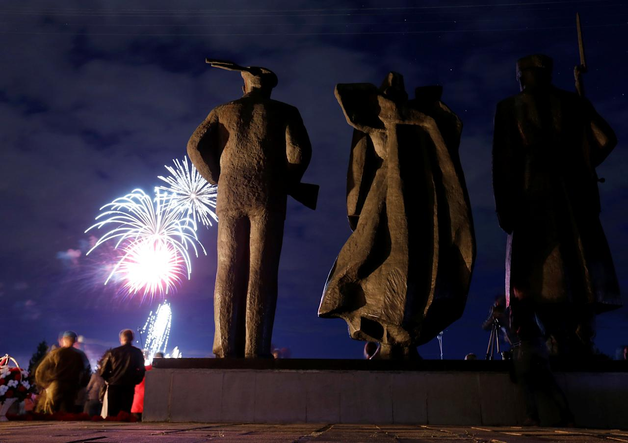 Spectators watch as fireworks explode in the sky in front of the Victory Monument, as part of festive commemorations for the 75th anniversary of the arrival of the first allied Arctic Convoy, Operation Dervish, at the northern port of the Soviet Union during World War Two, in Arkhangelsk, Russia, August 31, 2016  REUTERS/Maxim Zmeyev