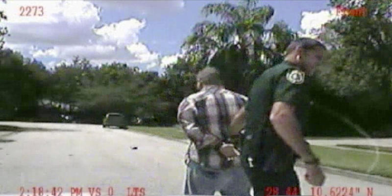 """In this image made from dash-cam video and released by the Lake Mary (Fla.) Police, George Zimmerman is detained by officers on Monday, Sept. 9, 2013 after Police in central Florida were called via 911 by Shellie Zimmerman saying her estranged husband was in his truck and threatening her and her father with a gun. Whether they think he got away with murdering 17-year-old Trayvon Martin or that he was just a brave neighborhood watch volunteer """"standing his ground,"""" many Americans can't seem to get enough of George Zimmerman. And he can't seem to stop giving it to them. (AP Photo/Lake Mary (Fla.) Police)"""