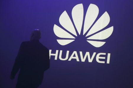 A man walks past a logo during the presentation the Huawei's new smartphone, the Ascend P7, launched by China's Huawei Technologies in Paris, May 7, 2014. REUTERS/Philippe Wojazer/Files