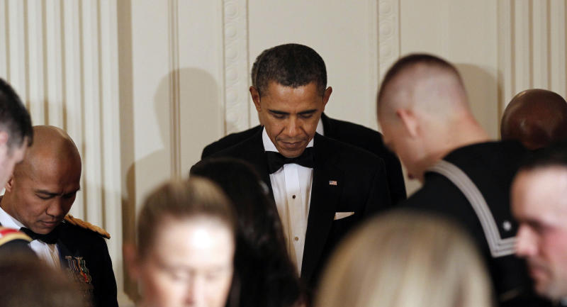 President Barack Obama bows his head during an opening prayer as he hosts a dinner for members of the U.S. military who served in Iraq in the East Room of the White House in Washington, Wednesday, Feb., 29, 2012. (AP Photo/Pablo Martinez Monsivais)