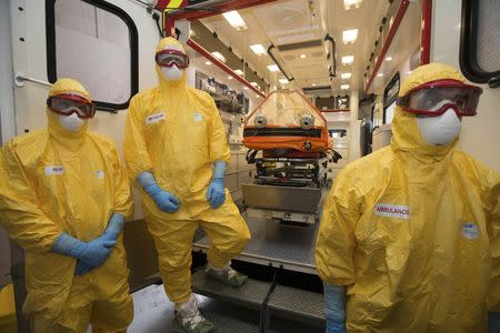 Staff of the emergency medical services in France (SAMU) dressed in Ebola virus protections outfits stand near a stretcher placed inside an ambulance during a press presentation
