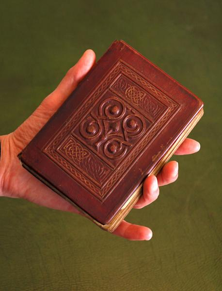 This photo, released by The British Library Tuesday April 17 2012, , shows the St. Cuthbert Gospel, a remarkably preserved palm-sized book which is a manuscript copy of the Gospel of John in Latin which was bought from the British branch of the Society of Jesus (the Jesuits), the library said Tuesday April 17, 2012. The small book - 96 mm (3.8 inches) by 136 mm (5.4 inches) - has an elaborately tooled red leather cover. It comes from the time of St. Cuthbert, who died in 687, and it was discovered inside his coffin at Durham Cathedral when it was reopened in 1104. (AP Photo / The British Library)