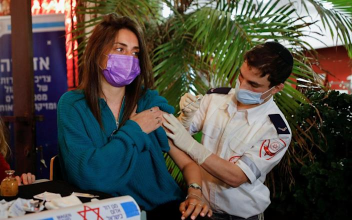 A woman receives a vaccination at a Tel Aviv bar offering free drinks with a Covid shot - CORINNA KERN/REUTERS