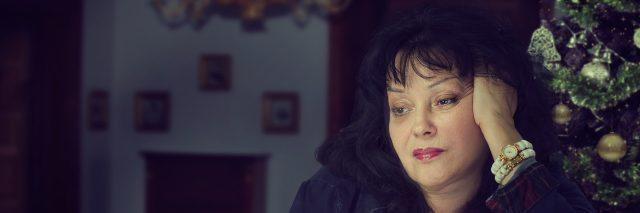 Black-haired mature woman is upset and frustrated about celebrating Christmas alone. Woman drinks coffee, head is propped up with her hand. Dark blurred indoors background with decorated tree
