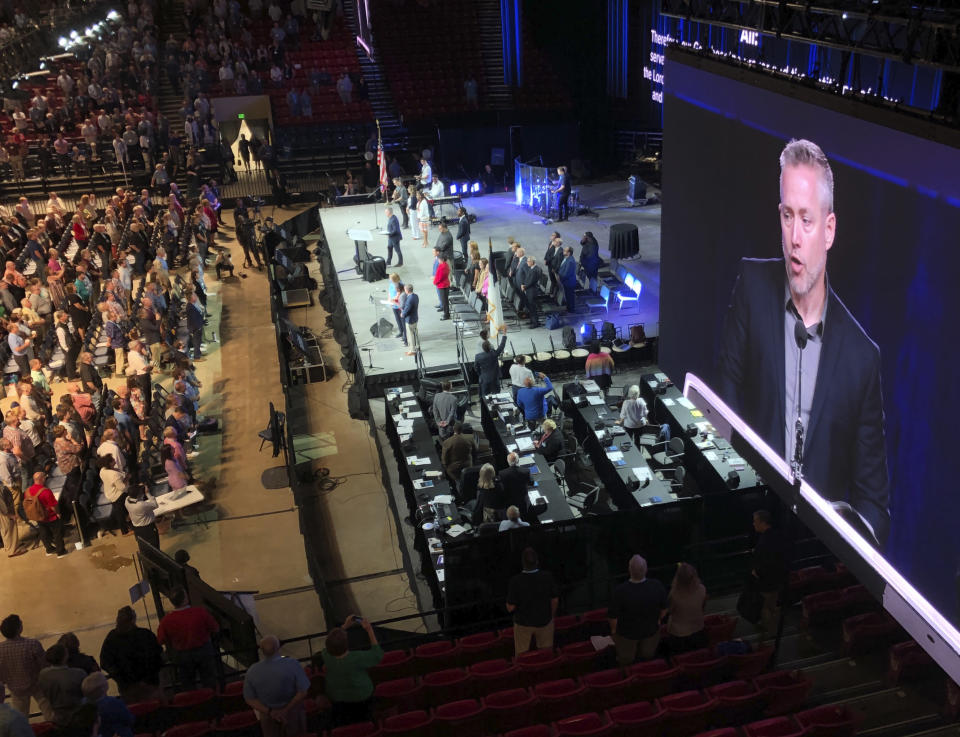 FILE - In this Wednesday, June 13, 2019 file photo, J.D. Greear, president of the Southern Baptist Convention, is shown on a video screen as he addresses the denomination's annual meeting in Birmingham, Ala. As Southern Baptists prepare for their biggest annual meeting in more than a quarter-century in June 2021, accusations that leaders have shielded churches from claims of sexual abuse and simmering tensions around race threaten to once again mire the nation's largest Protestant denomination in a conflict that can look more political than theological. (AP Photo/Jay Reeves, File)