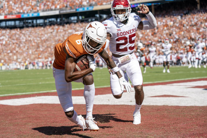 Texas wide receiver Joshua Moore (6) comes down with a touchdown reception in front of Oklahoma defensive back Justin Broiles (25) during the first half of an NCAA college football game at the Cotton Bowl, Saturday, Oct. 9, 2021, in Dallas. (AP Photo/Jeffrey McWhorter)