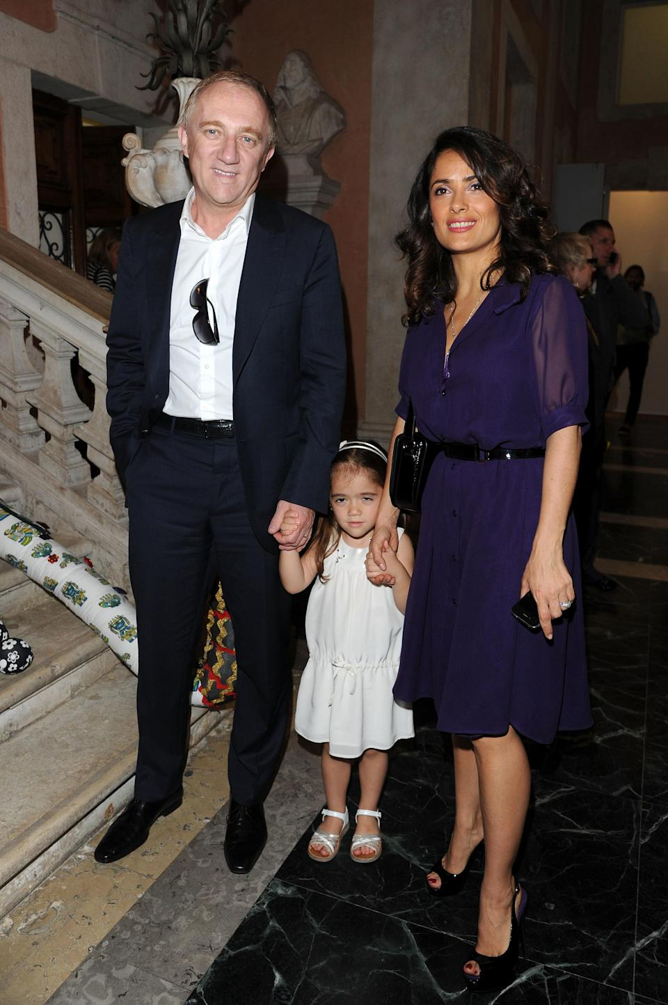 Salma and François-Henri hold hands with a young Valentina