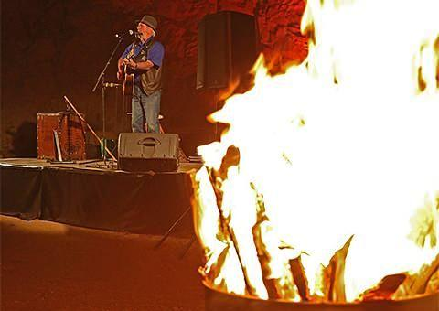 Bushfire ballads: An open fire and live music during the Outback barbecue on the Ghan Anzac tribute train. Photo: Cristal Bettany for Total Travel