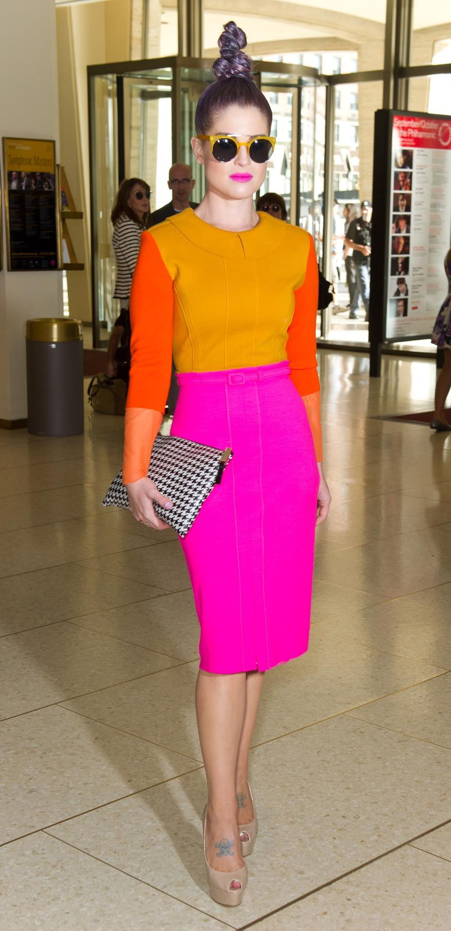 """Violet haired Kelly Osbourne definitely isn't one to shy away from taking risks with color. """"Getting ready to go see the @cmbenz presentation! The dress Im wearing is the most amazingly neon orange and pink dress ever!"""" Kelly tweeted when she wore this light orange, dark orange and hot pink outfit."""
