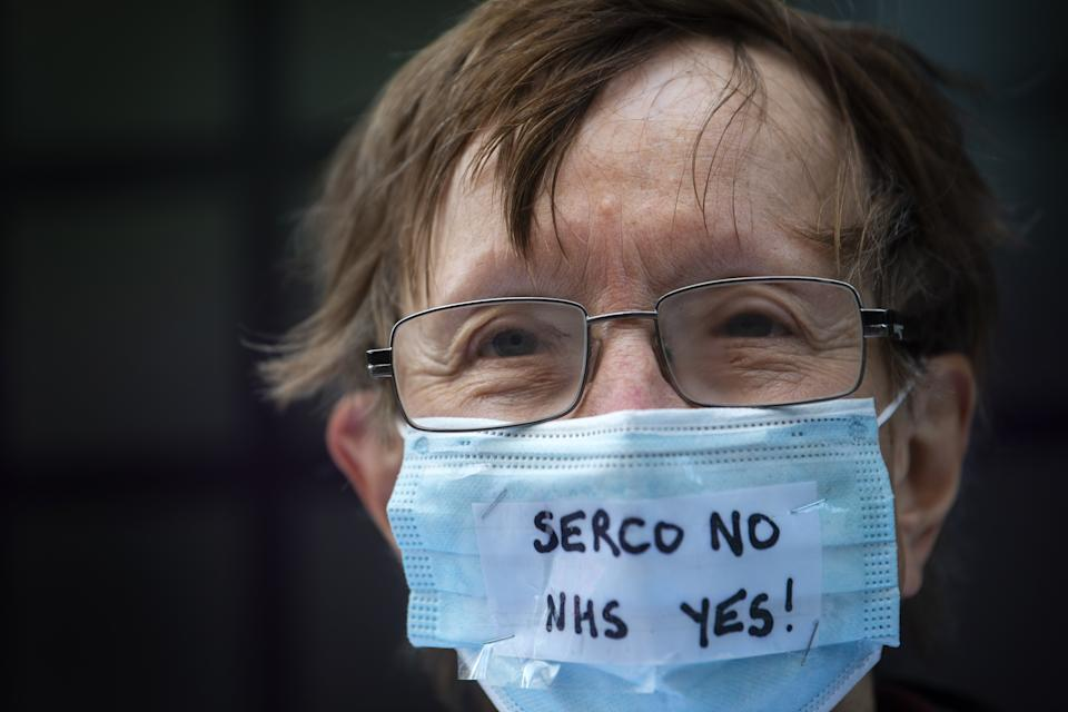 A campaigner outside the Department of Health and Social Care office in London protesting over Serco's handling of the test, track and trace system.