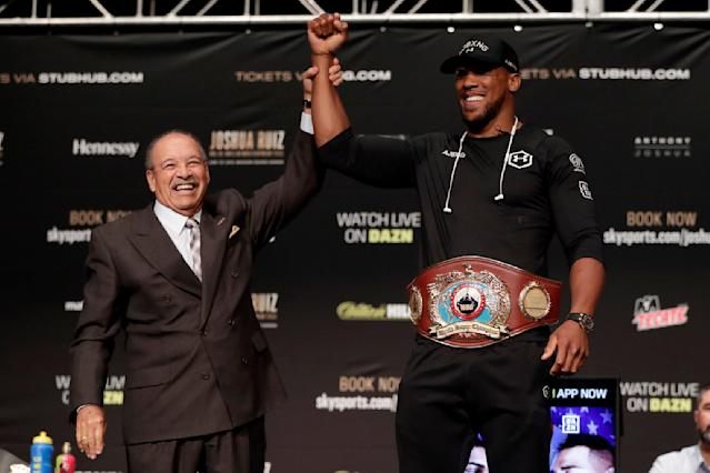 Francisco Varcarcel, left, president of the World Boxing Organization, holds the arm of British boxer Anthony Joshua after presenting him with the WBO belt during a press conference ahead of his heavyweight bout against Andy Ruiz, Thursday, May 30, 2019, in New York. Joshua will defend his WBA, WBO and IBF heavyweight titles. (AP Photo/Julio Cortez)