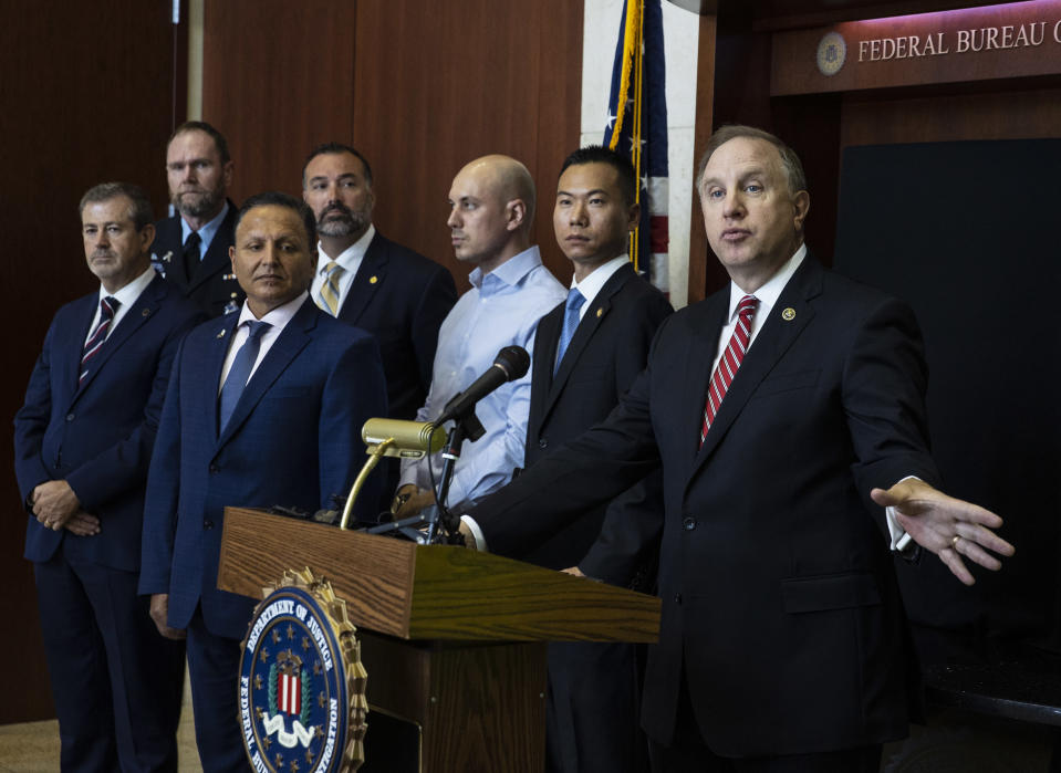 Special Agent in Charge Aaron Rouse of the FBI Las Vegas Field Office speaks as Acting U.S. Attorney Christopher Chiou, second right, looks on during a news conference at the FBI Las Vegas Field Office, Wednesday, July 14, 2021, in Las Vegas. U.S. officials declared they dismantled a key international cocaine and money-laundering hub in an ongoing investigation that began in Las Vegas and has involved at least 30 other countries. The top federal prosecutor and FBI chief in Las Vegas said the recent arrests of six people in Nevada, Arizona, California and Washington state came as part of the six-year probe. (Bizuayehu Tesfaye/Las Vegas Review-Journal via AP)