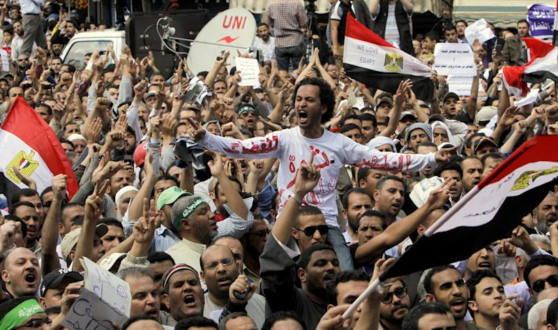 "Egyptian Muslim Brotherhood members shout slogans during a protest in front of the Supreme Judicial Council in Cairo, Egypt, Friday, April 19, 2013. Arabic on the T-shirt reads, ""clean judiciary."" Thousands of supporters of Egypt's Islamist president have taken to the streets of Cairo, calling on him to ""cleanse the judiciary."" Mohammed Morsi and the judiciary have had tense relations since he came to power in June last year. Judges accused him of trampling on their authority, while Morsi supporters charge that the judiciary is controlled by supporters of ousted President Hosni Mubarak. (AP Photo/ Amr Nabil)"