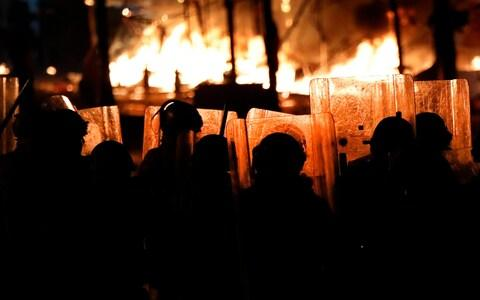 Riot policemen watch flames rise from the tents of the anti-government protesters - Credit: AP