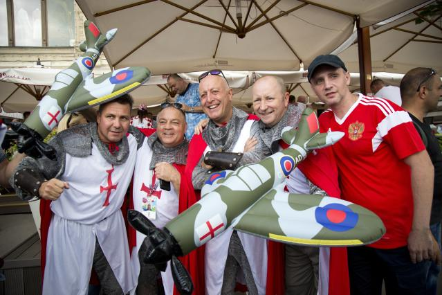 <p>England fans pose for a photo with a Russian fan, right, at a bar in Red Square – complete with inflatable Spitfires. </p>
