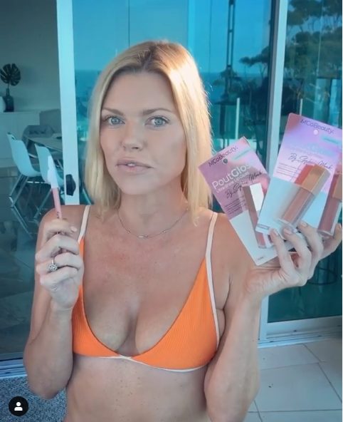 A photo of Sophie Monk wearing an orange bikini holding beauty products.