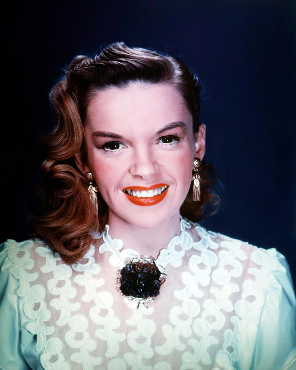 Garland wears a white lace blouse with and gold drop earrings in a studio portrait, circa 1950.