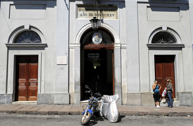 People stand outside Maciel public hospital in Montevideo, Uruguay, Sunday March 18, 2012. Uruguayan police say an investigation into dozens of possibly induced deaths at two hospitals, including Maciel, has led to the detention of at least two people. Police inspector Jose Luis Roldan said Sunday that officials suspect that hospital workers brought a sort of poison from Brazil and gave it to patients who were in critical condition. (AP Photo/Matilde Campodonico)