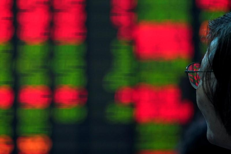 FILE PHOTO: An investor looks at an electronic board showing stock information at a brokerage house in Shanghai, China July 6, 2018. REUTERS/Aly Song/File Photo
