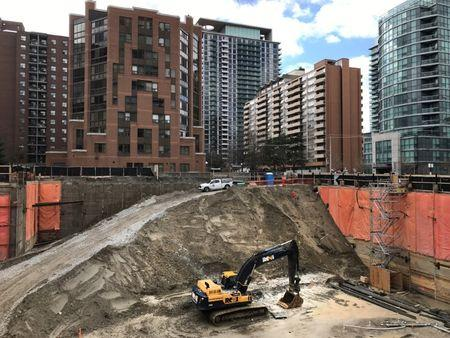 Construction equipment is parked at the bottom of a pit on the site of a new condominium complex in Toronto