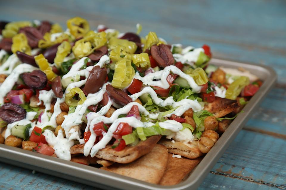 "<p>Everything you love about a Greek salad—but way more fun! Delivering a perfect blend of flavor and texture in every bite, these loaded nachos are the perfect snack to throw together for your next at-home movie night or tailgate party. This recipe is an excellent way to give a new life to leftover rotisserie chicken and veggie scraps kicking around your fridge. Feel free to use store bought pita chips rather than baking your own. </p> <p><a href=""https://www.myrecipes.com/recipe/loaded-greek-salad-nachos"" rel=""nofollow noopener"" target=""_blank"" data-ylk=""slk:Loaded Greek Salad Nachos Recipe"" class=""link rapid-noclick-resp"">Loaded Greek Salad Nachos Recipe</a></p>"