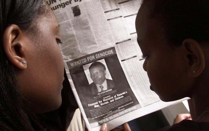 Readers look at a newspaper on June 12, 2002 in Nairobi carrying the photograph of Felicien Kabuga wanted by the United States - REUTERS