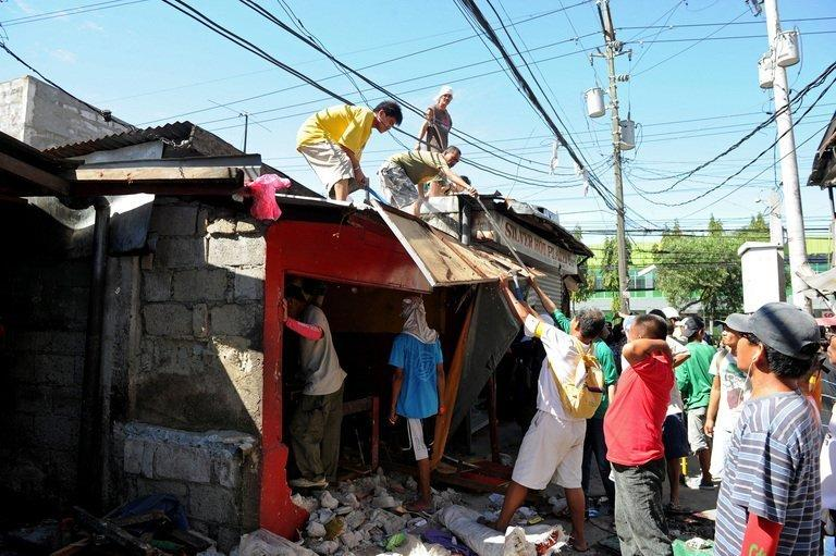 Members of a demolition crew dismantle a house at a slum area in suburban Manila on April 24, 2012. Experts have warned that flooding in Manila has been worsened by the squatter communities who build precarious shanties on the banks of waterways, preventing water from flowing freely and blocking drains with rubbish