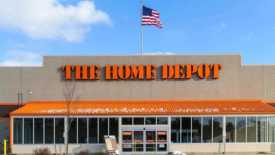 """""""Wareham, Massachusetts, USA-January 7, 2013: An American flag flies over the entrance and outside facade of a large Home Depot store that sells a full range of building matrerials and home products."""