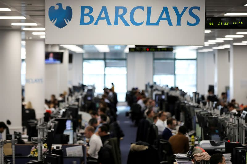 FILE PHOTO: Traders work on the trading floor of Barclays Bank at Canary Wharf in London