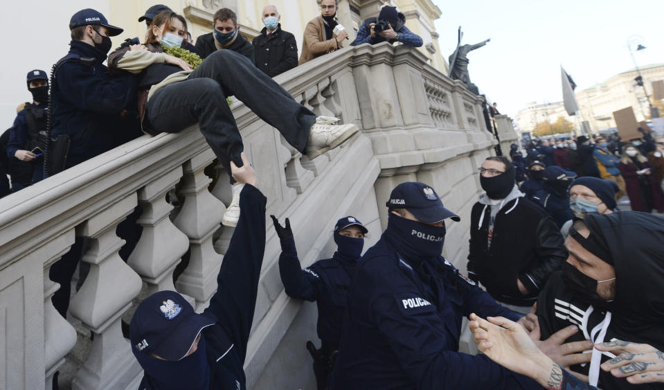 Members of a far-right organization and police remove women from a church where they were protesting church support for tightening Poland's already restrictive abortion law in Warsaw, Poland, Sunday, Oct. 25, 2020. Poland constitutional court issued a ruling on Thursday that further restricts abortion rights in Poland, triggering four straight days of protests across Poland. (AP Photo/Czarek Sokolowski)