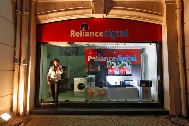 An employee leaves a store of Reliance Industries Ltd, controlled by Mukesh Ambani, one of India's richest men, at a market in Kolkata