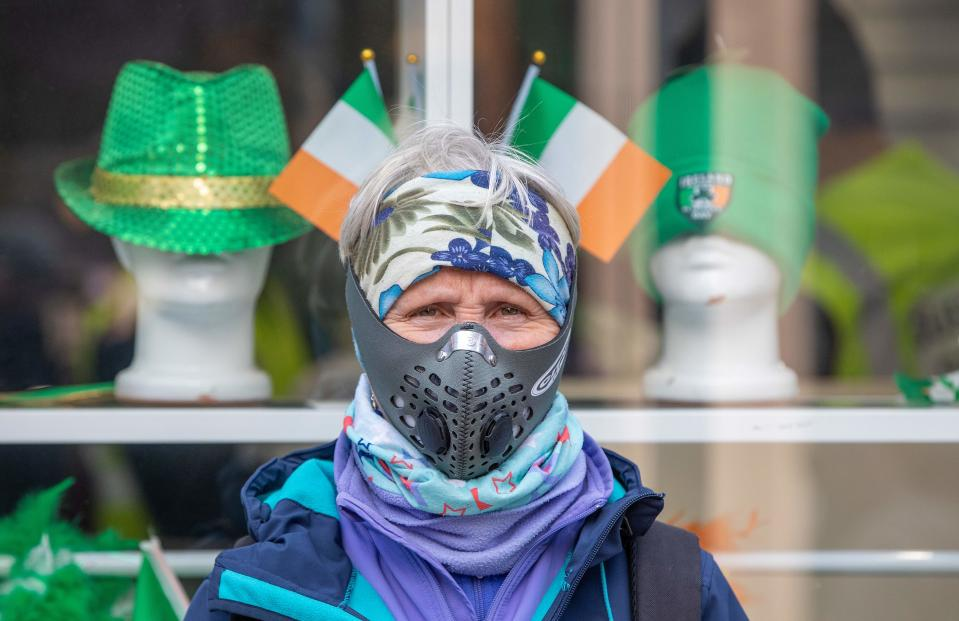 "Breda Brody, a former Nurse, poses for a picture wearing a filter mask in the Grafton shopping area of in Dublin on March 12, 2020. - Ireland on Thursday announced the closure of all schools and colleges, and recommended the cancellation of mass gatherings as part of measures to combat the spread of the coronavirus. Prime Minister Leo Varadkar said ""schools, colleges and childcare facilities will close from tomorrow (Friday)"", as would state-run cultural institutions. (Photo by Paul Faith / AFP) (Photo by PAUL FAITH/AFP via Getty Images)"