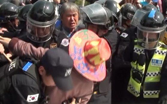 A protester fights with police amid the demonstration - Credit: NO THAAD SOSEONG-RI TASK FORCE