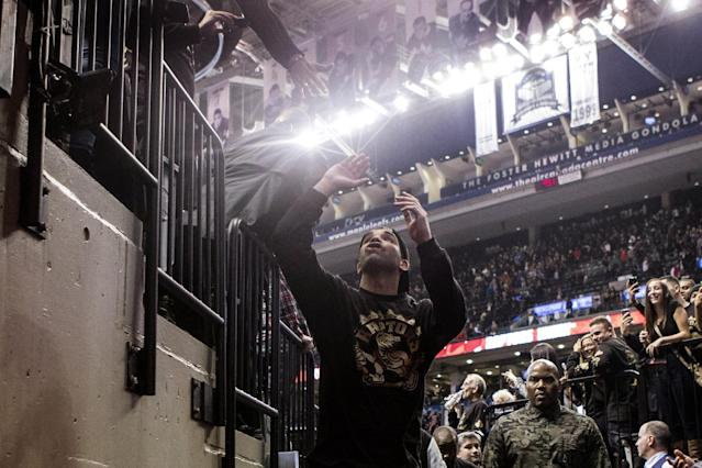 Rapper Drake high fives a fan as he leaves the court following Toronto Raptors 96-80 win over Brooklyn Nets in an NBA basketball game, Saturday, Jan. 11, 2014 in Toronto (AP Photo/The Canadian Press, Chris Young)