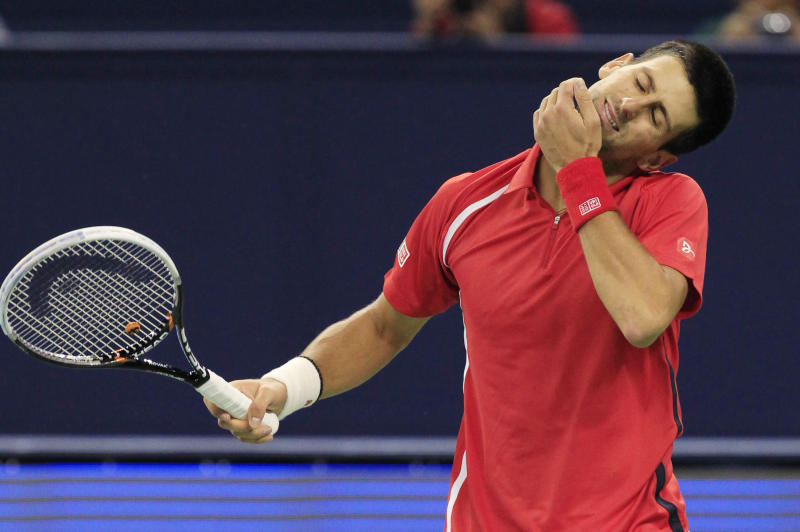 Novak Djokovic of Serbia stretches his neck in the men's singles semifinal match against Tomas Berdych of the Czech Republic at the Shanghai Masters tennis tournament at Qizhong Forest Sports City Tennis Center in Shanghai, China, Saturday Oct. 13, 2012. Djokovic won 6-3, 6-4. (AP Photo/Eugene Hoshiko)