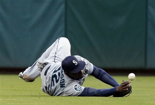 Seattle Mariners left fielder Trayvon Robinson (12) dives for and is unable to catch a fly ball hit by Texas Rangers' Michael Young in the seventh inning during a baseball game Sunday, Sept. 16, 2012, in Arlington, Texas. The Rangers won 2-1. (AP Photo/Jim Cowsert)