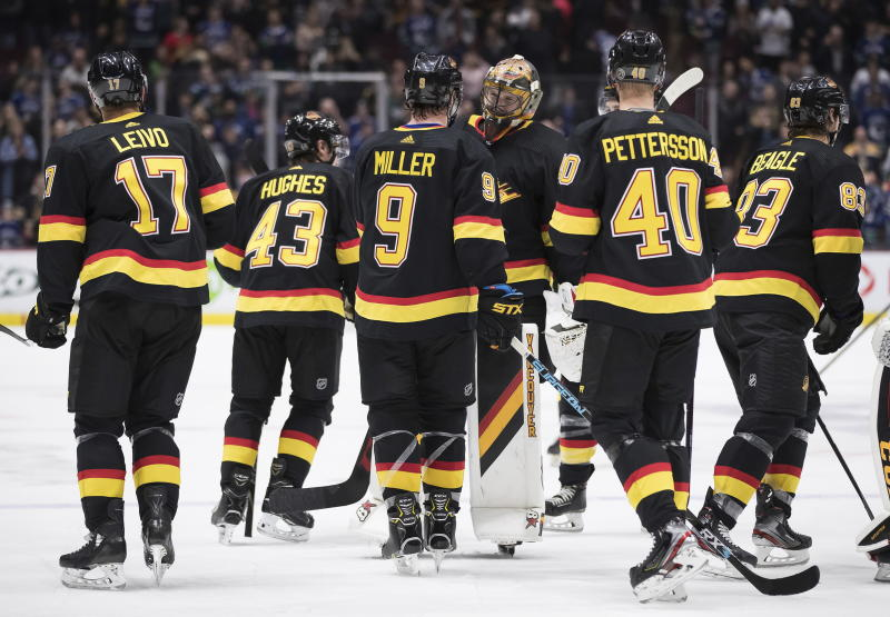 Vancouver Canucks goalie Thatcher Demko, back center, and J.T. Miller (9) celebrate Miller's winning goal against the Buffalo Sabres during overtime of an NHL hockey game in Vancouver, British Columbia, Saturday, Dec. 7, 2019. (Darryl Dyck/The Canadian Press via AP)