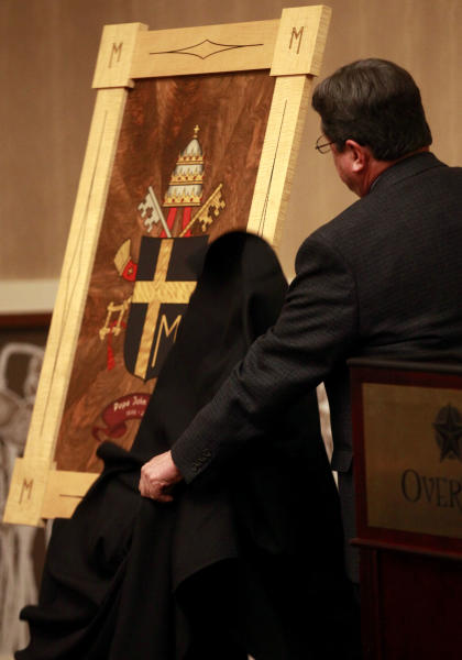 Chancellor of The Catholic Diocese of Lubbock Marty Martin unveils the coat of arms of Pope John Paul II at the Overton Hotel and Conference Center during an announcement of an exhibit displaying artifacts from Pope John Paul the II is coming to Lubbock, Thursday, Nov. 29, 2012. The coat of arms is inlay wood made from 21 different types of wood. Over 130 items are expected to be on display between March 15, 2013 and May 31, 2013 at The Catholic Renewal Center of the Diocese of Lubbock. (AP Photo/Lubbock Avalanche-Journal, Stephen Spillman)