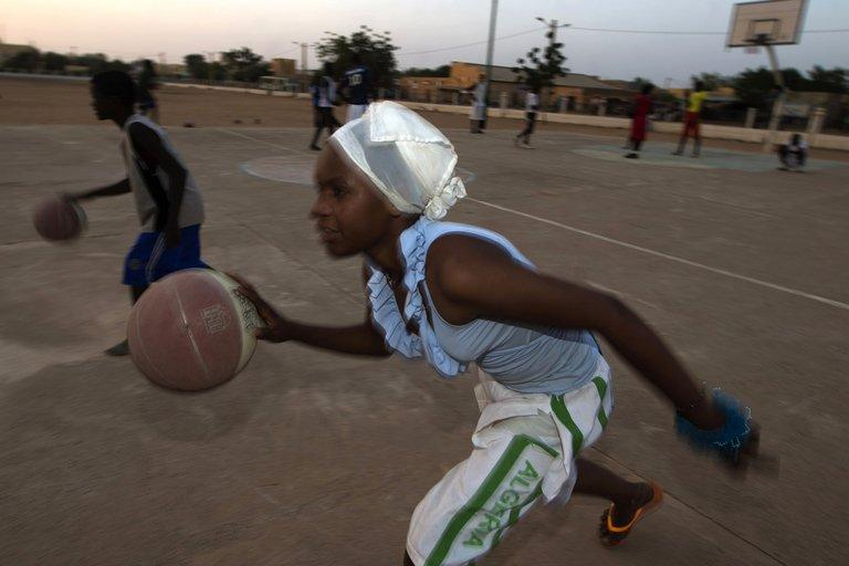 """Fatoumata, 16, plays basketball at the former """"Sharia Square"""" in central Gao, on February 26, 2013. Since the departure of the Islamists, who occupied the city for nine months, following the arrival of the French and Malian forces, the central square of Gao is once again called """"Independence square."""""""