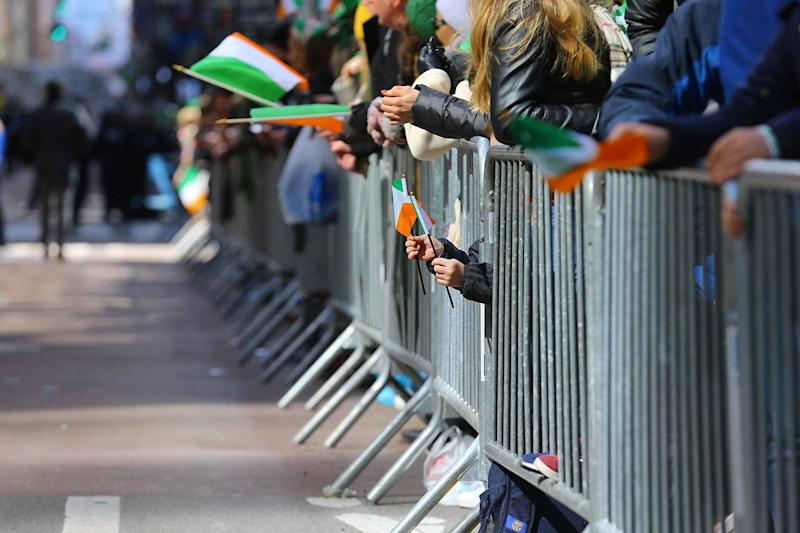 A youngster holds two flags of Ireland through the barricade during the St. Patrick's Day Parade, March 16, 2019, in New York. (Photo: Gordon Donovan/Yahoo News)