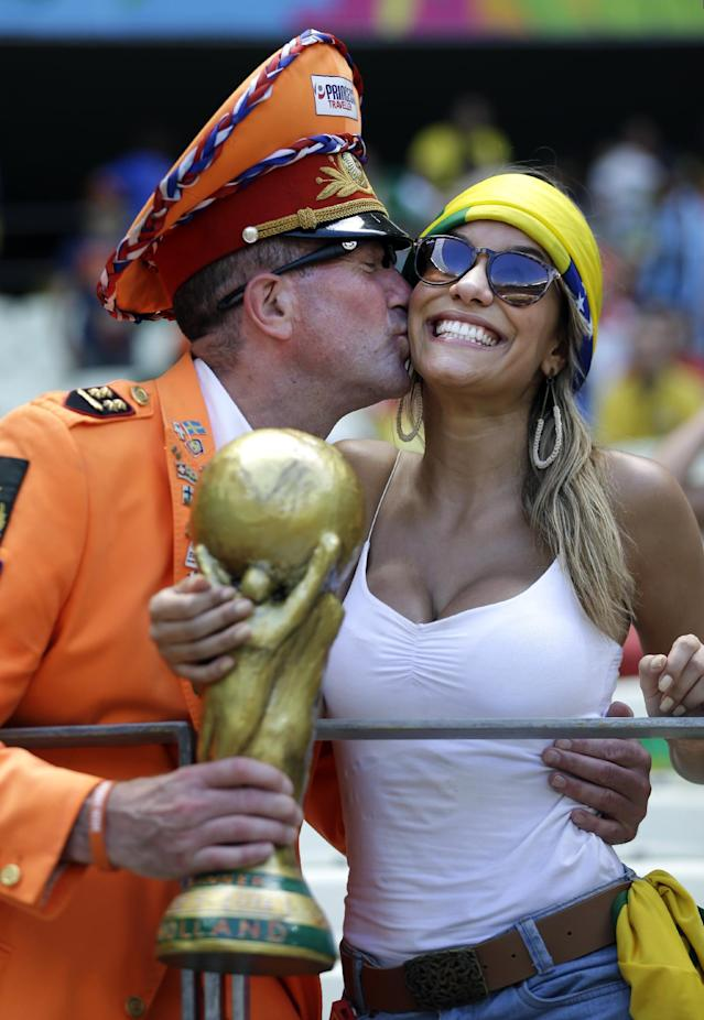 A Dutch supporter kisses a Brazilian fan before the World Cup round of 16 soccer match between the Netherlands and Mexico at the Arena Castelao in Fortaleza, Brazil, Sunday, June 29, 2014. (AP Photo/Natacha Pisarenko)