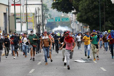 Opposition supporters clash with security forces during a rally against Venezuela's President Nicolas Maduro in Caracas