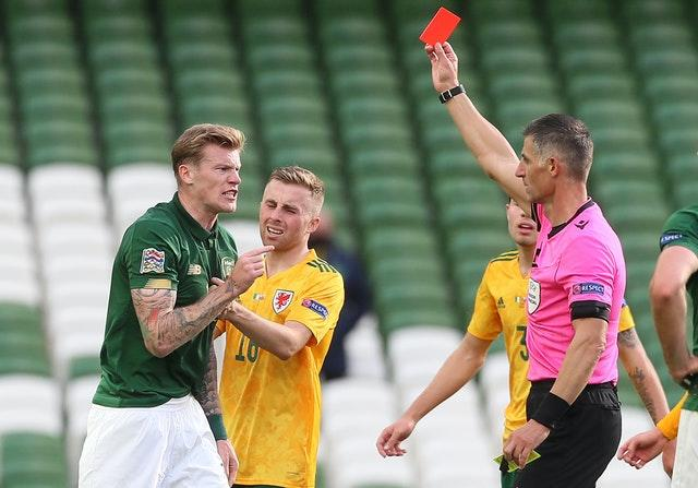 Referee Anastasios Sidiropoulos shows a red card to Ireland's James McClean