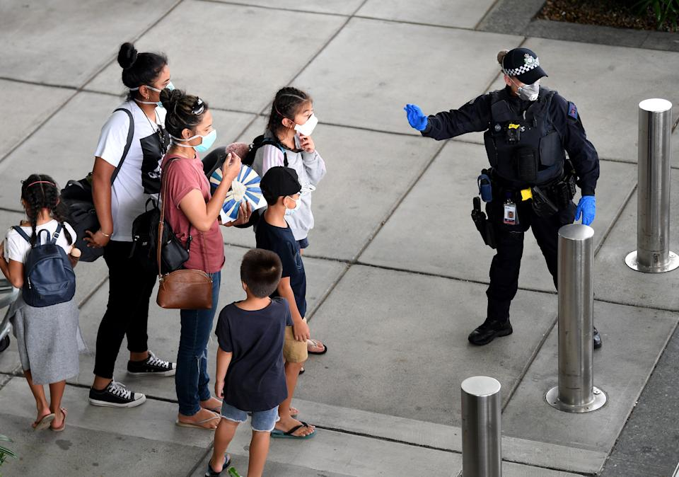A police officer directs passengers who came on a special international repatriation flight in Brisbane. Source: AAP
