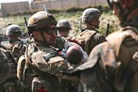 In this image courtesy of the US Central Command Public Affairs, a US airman comforts an infant during an evacuation at Hamid Karzai International Airport