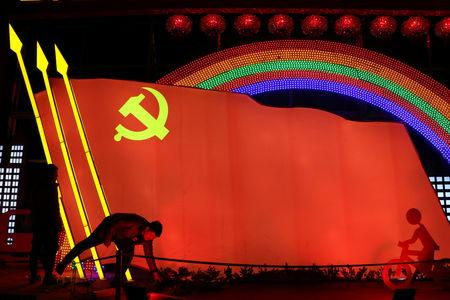 FILE PHOTO: Men check on a light installation in a shape of the party flag of the Communist Party of China, that is set up to celebrate the upcoming Chinese Lunar New Year, in Jining, Shandong