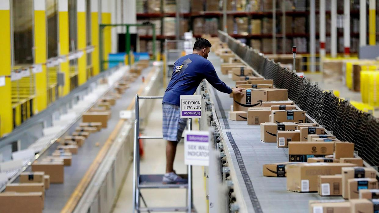 Mandatory Credit: Photo by AP/REX/Shutterstock (8979717e)An Amazon employee makes sure a box riding on a belt is not sticking out at the Amazon Fulfillment center in Robbinsville Township, N.