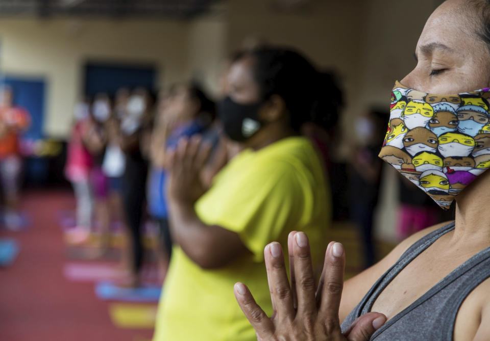 "Residents take part in a free yoga class sponsored by the ""Treino na Laje"" project that aims to recover people's self-esteem through yoga, in Capao Redondo favela, in Sao Paulo, Brazil, Saturday, Oct. 24, 2020, as restrictions related to COVID-19 pandemic are eased. The project also distributes donated food and toys for poor children, performs social actions and administers free sports classes. (AP Photo/Carla Carniel)"