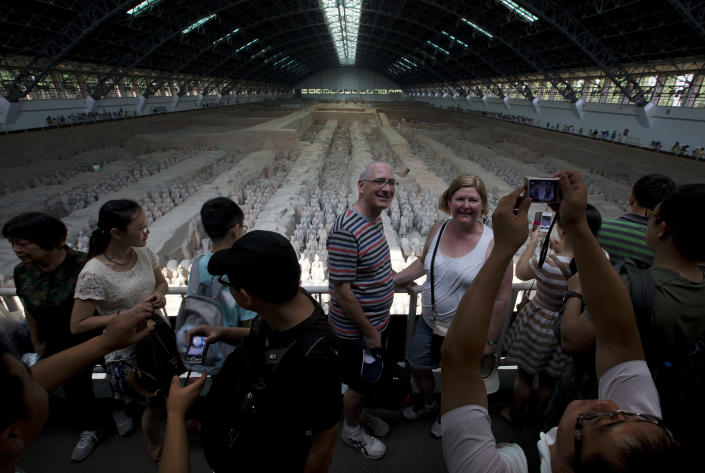 "In this Tuesday, July 30, 2013 photo, foreign and local tourists have photos taken near a display of unearthed terracotta warriors as they visit an excavation site at the Museum of Qin Terracotta Warriors and Horses in Xi'an, in central China's Shaanxi province. China's new tourism slogan ""Beautiful China"" has been criticized by industry experts who say it illustrates a marketing problem that has led to a weakness in growth in foreign visitors over the past few years. (AP Photo/Andy Wong)"